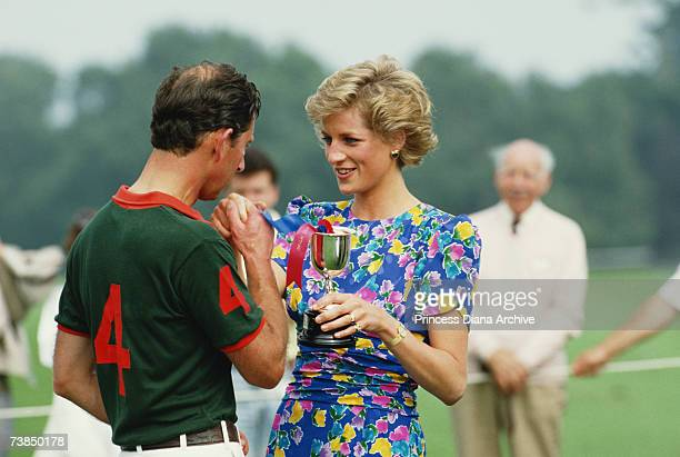 Princess Diana wearing a Belville Sassoon dress presenting Prince Charles with a trophy after competing at the Hola Cup polo match at the Guards Polo...