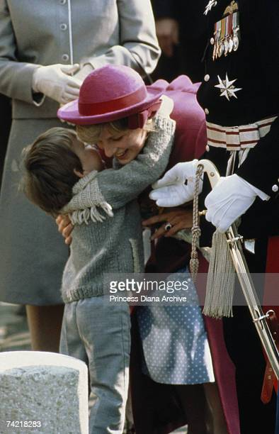 Princess Diana wearing a John Boyd hat hugs a small boy during a visit to the Chinatown district of Liverpool April 1982