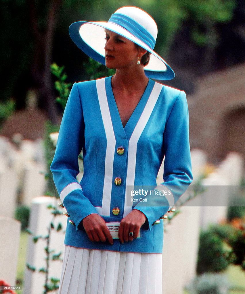 Princess Diana wearing blue & white top, white pleated skirt & white wide-brimmed hat w. blue band during a tour of India.