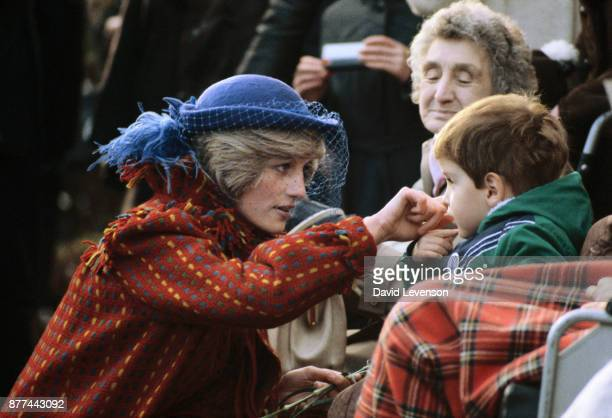 Princess Diana with a young boy during a visit to Wrexham Wales on November 28 1982 She is wearing a coat by Bellville Sassoon and a hat by John Boyd