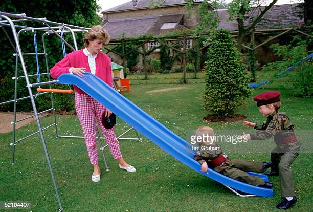 Princess Diana With Her Sons Prince William And Prince Harry Playing On A Slide In The Gardens Of Highgove House. The Boys Are Wearing The Uniforms...