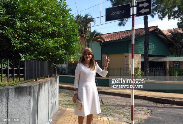 Princess Dina Mired of Jordan Presidentelect of the International Union Against Cancer poses pointing at a street sign with the name of her country...