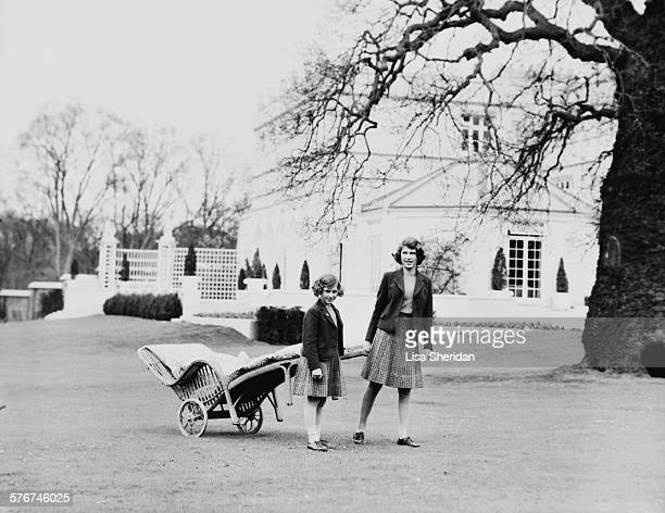 Princess Elizabeth and her sister Princess Margaret pulling a lawn chair on wheels in the terraces at the back of the Royal Lodge Windsor UK April...