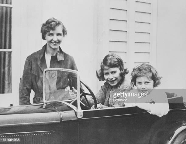 Princess Elizabeth and her younger sister Princess Margaret of Great Britain play in a miniature automobile while their governess, Marion Crawford,...