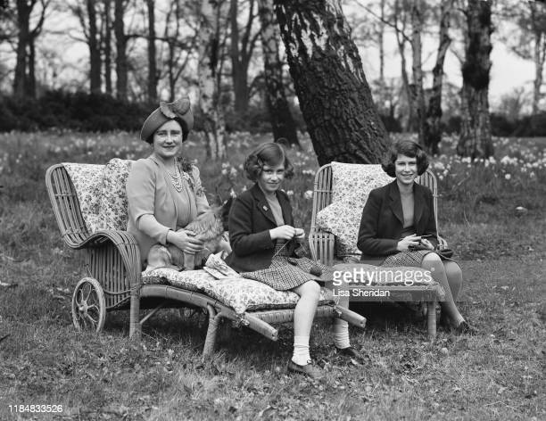 Princess Elizabeth and her younger sister Princess Margaret sits on deckchairs while knitting for the forces next to their mother Elizabeth BowesLyon...