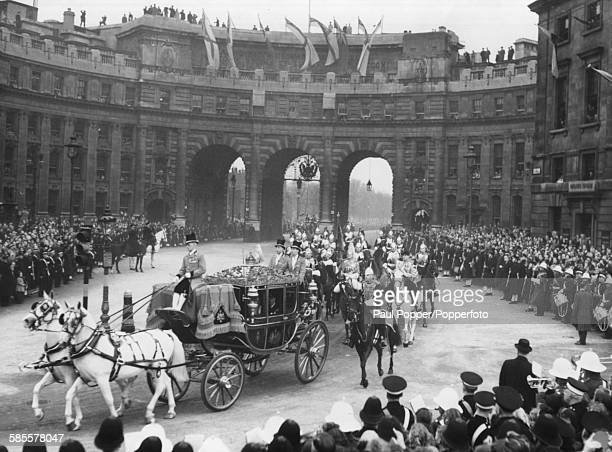 Princess Elizabeth and King George VI ride in the Irish State Coach past crowds of people through Admiralty Arch and on their way to Westminster...