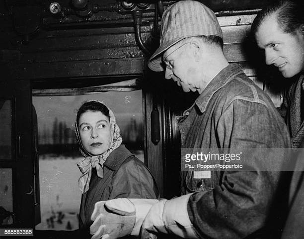 Princess Elizabeth and Prince Philip talk to engineer A McPhail on the footplate of a steam locomotive hauling the royal train to Edmonton in Alberta...