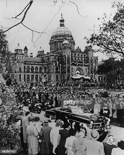 Princess Elizabeth and Prince Philip the Duke of Edinburgh drive away from the British Columbia Parliament Buildings past crowds of onlookers during...