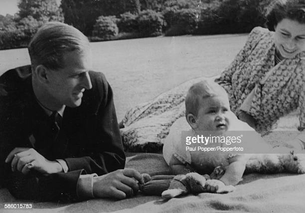 Princess Elizabeth and Prince Philip the Duke of Edinburgh playing with their young son Prince Charles in the gardens of the royal residence of...