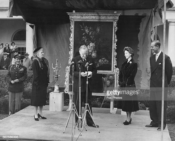 Princess Elizabeth and Prince Philip the Duke of Edinburgh smiling as President Harry Truman gives a speech and his aide General Harry Vaughan looks...