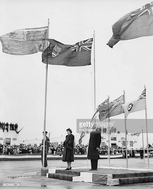 Princess Elizabeth and Prince Philip the Duke of Edinburgh standing beneath the raised flags including the Princess's Standard during a ceremony at...