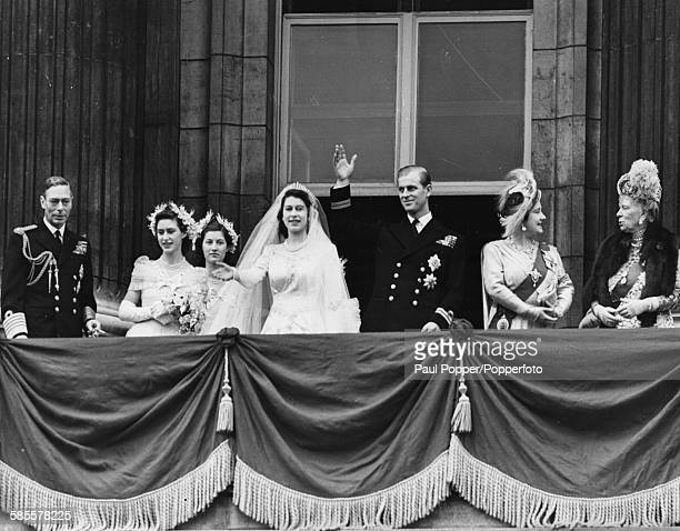 Princess Elizabeth and Prince Philip wave from the balcony of Buckingham Palace following their wedding ceremony, with King George VI, Princess...