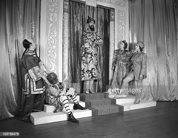 Princess Elizabeth and Princess Margaret both in costume pictured alongside fellow performers during a royal pantomime production of 'Aladdin' at...