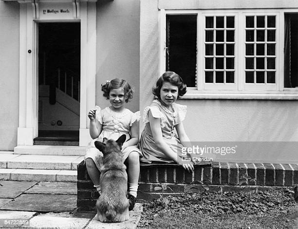 Princess Elizabeth and Princess Margaret play with a corgi outside the Welsh House at the Royal Lodge Windsor June 1936