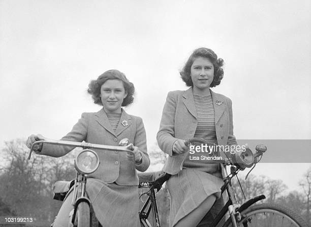Princess Elizabeth and Princess Margaret pose on bicycles in Windsor, England on April 4, 1942.