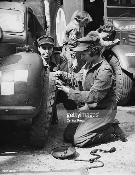 Princess Elizabeth changing the tire of a vehicle as she trains at as ATS Officer during World War Two, at the ATS training centre in England, April...