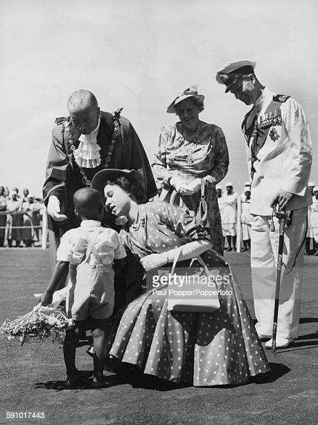 Princess Elizabeth crouches down to receive a bouquet from young Prince Selim watched by the Mayor of Nairobi Alderman J R Maxwell his wife and...