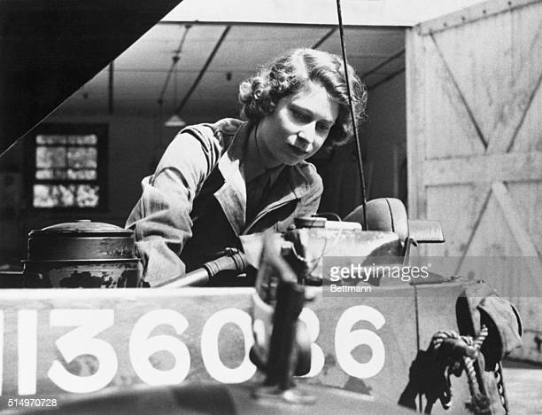 Princess Elizabeth heir apparent to the throne of England is shown checking the motor of an army vehicle during her training at an auxiliary...
