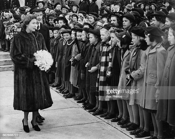 Princess Elizabeth holding a bouquet of flowers as she inspects a group of Brownies in uniform, during a Royal visit to Regina, Saskatchewan, October...