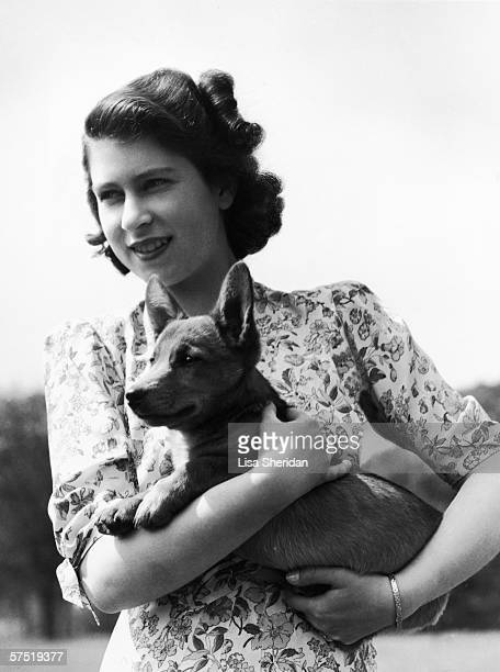 Princess Elizabeth holding Sue a corgi pup in the grounds of Windsor Castle Berkshire 30th May 1944