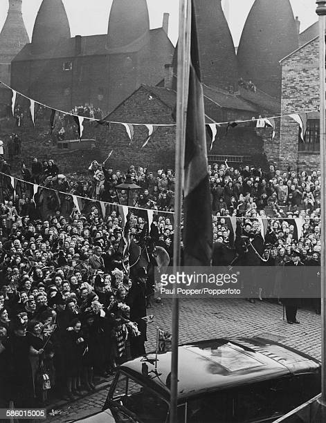 Princess Elizabeth is greeted by cheering crowds as she arrives in the Royal car at the Paragon China factory against the backdrop of Pot Banks or...
