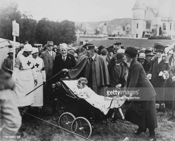Princess Elizabeth is pushed in a pram by a nanny alongside her grandfather King George V as they attend a fete at Balmoral Castle near Braemar in...