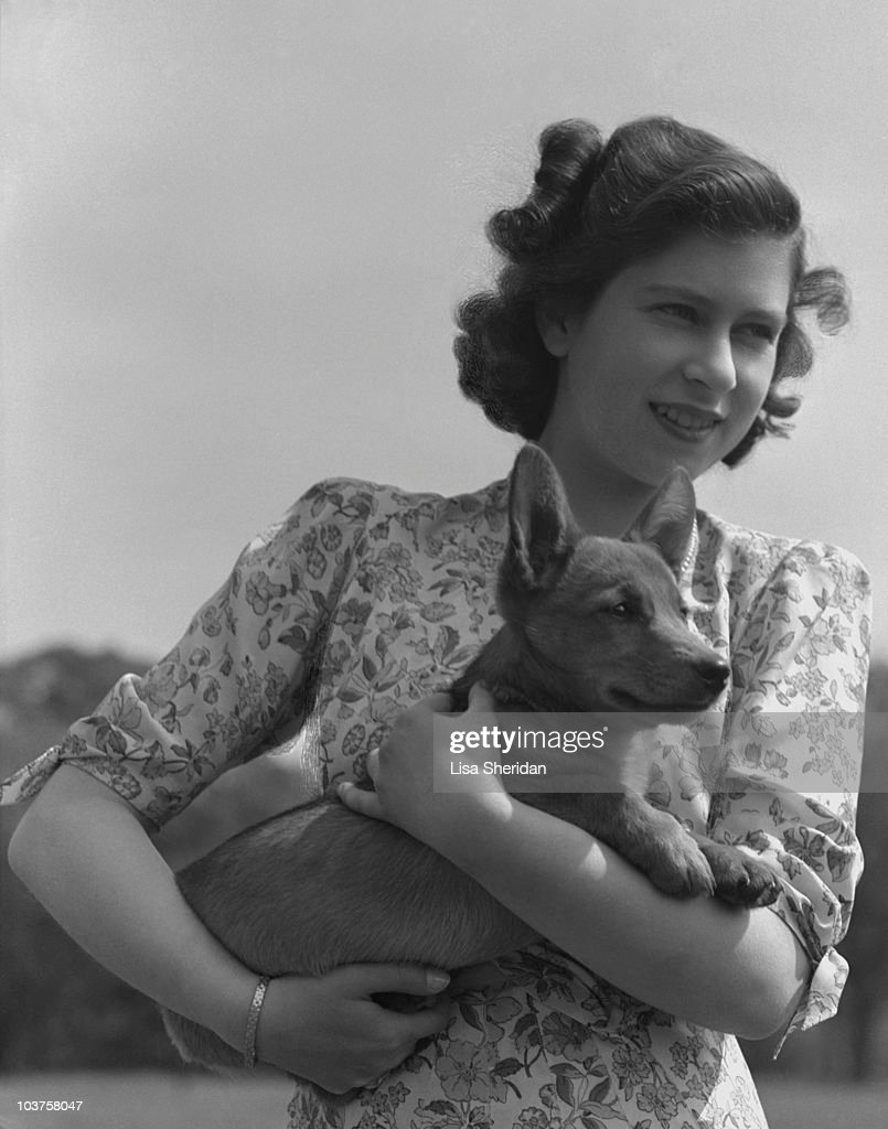 Princess Elizabeth (Queen Elizabeth II) pictured holding a corgi in the grounds of Windsor Castle, Berkshire, Great Britain, 30 May 1944.