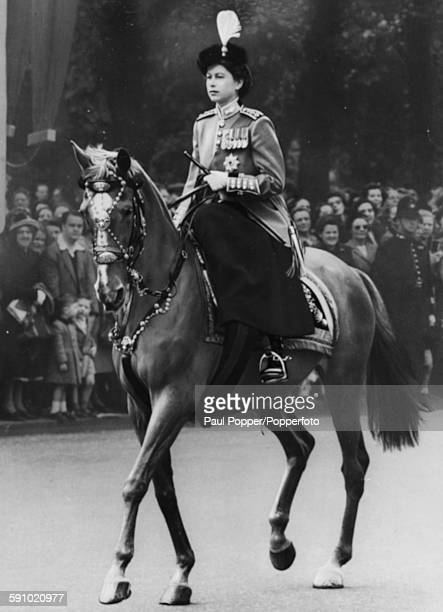 Princess Elizabeth pictured wearing a scarlet and gold tunic bearskin tricorne hat with osprey plume and Order of the Garter emblem as she rides the...