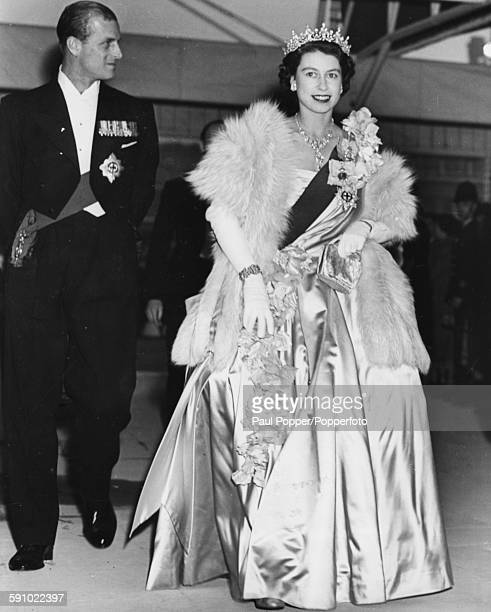 Princess Elizabeth pictured wearing an evening gown tiara and fur shawl as the attends an inaugural concert with Prince Philip Duke of Edinburgh at...