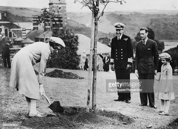 Princess Elizabeth plants a tree in the grounds of the Royal Naval College watched by King George VI and Princess Margaret at Dartmouth England in...