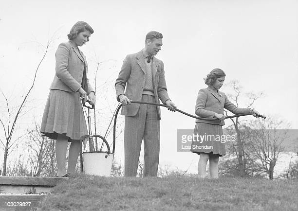 Princess Elizabeth pumps water from a bucket as King George VI and Princess Margaret hold a hose at the Royal Lodge in Windsor Castle England on...