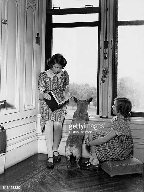 Princess Elizabeth reads to her sister Princess Margaret and Jane the corgi by a window in Windsor Castle. Princess Elizabeth is the future Queen...