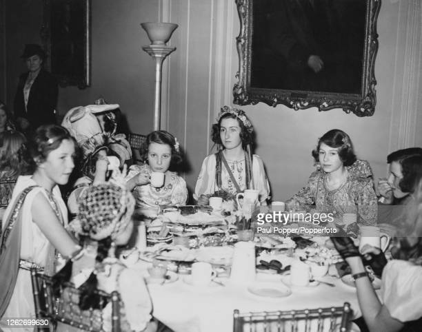 Princess Elizabeth , seated 2nd from right, taking tea with other young guests, including Princess Margaret, attending a children's fancy dress party...