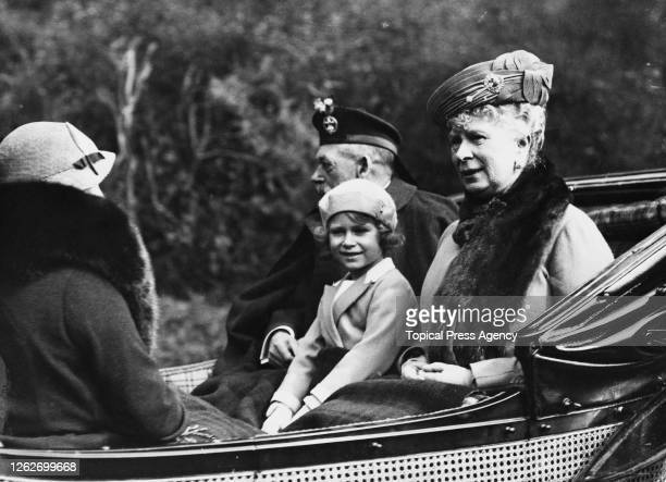 Princess Elizabeth seated between her grandfather King George V and grandmother Queen Mary of Teck as they ride in a carriage back to Balmoral Castle...