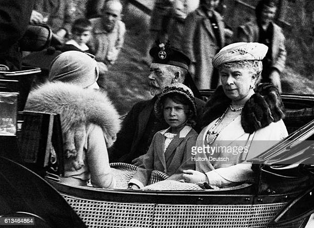 Princess Elizabeth sits between her grandparents, King George V and Queen Mary of England, facing her mother Elizabeth, the Duchess of York, as the...