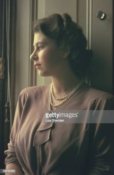 Princess Elizabeth standing by a window in the State Apartments at Buckingham Palace