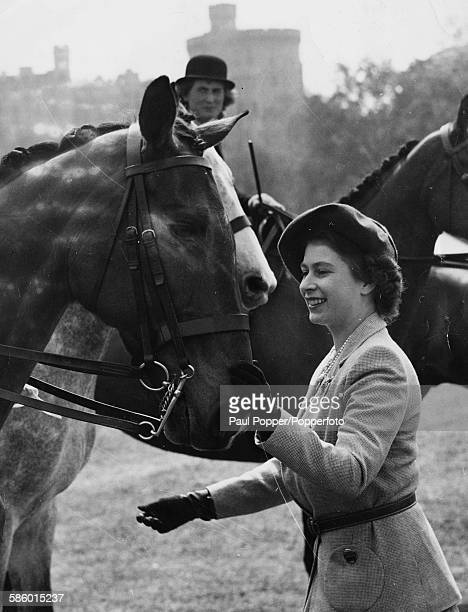 Princess Elizabeth strokes the horse 'Holyport' before presenting the third prize rosette to owner Mrs Selwyn Butcher at the Royal Windsor Horse Show...