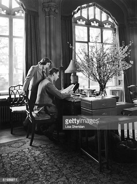 Princess Elizabeth watches her father King George VI at work at his desk in the Royal Lodge Windsor 11th April 1942