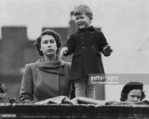 Princess Elizabeth watches Prince Charles smile at the crowds as they wait to view the marriage procession of Queen Juliana and Prince Bernhard to...