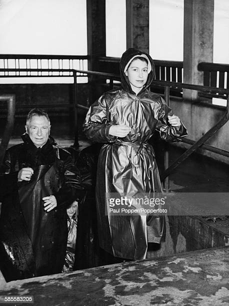 Princess Elizabeth wears a raincoat as she climbs up steps to the observation platform at the foot of Niagara Falls Ontario Canada on October 14th...