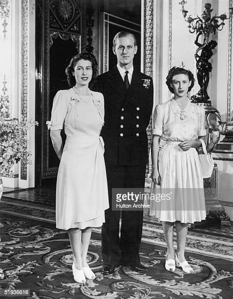 Princess Elizabeth with her fiance Lieutenant Philip Mountbatten and her sister Margaret in the White Drawing Room of Buckingham Palace September...