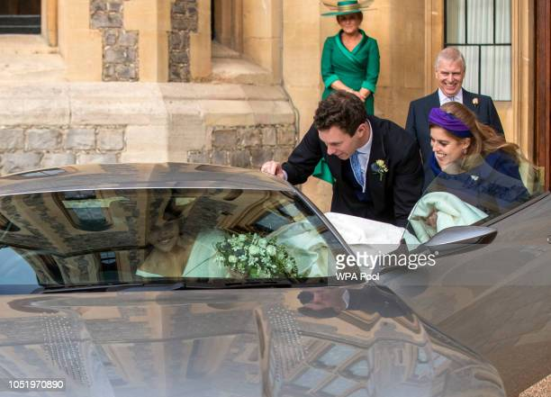 Princess Eugenie and Jack Brooksbank helped by Princess Beatrice and Prince Andrew Duke of York leave Windsor Castle in an Aston Martin DB10 after...
