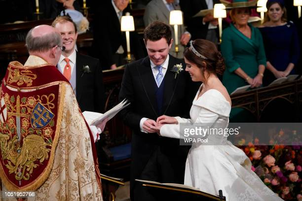 Princess Eugenie smiles as Jack Brooksbank put the ring on her finger during their wedding ceremony at St George's Chapel in Windsor Castle on...