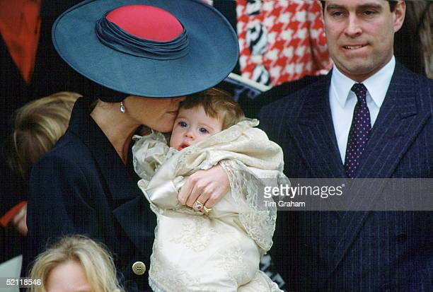 Princess Eugenie's Christening At Sandringham Church. Her Mother, The Duchess Of York, Is Giving Her A Kiss As Prince Andrew Looks On.