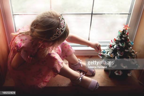 Princess girl in window sill with small tree