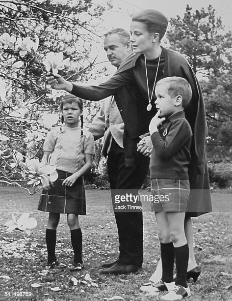 Princess Grace of Monaco examines a flower during a visit to her childhood home surrounded by her family from left daughter Princess Caroline her...