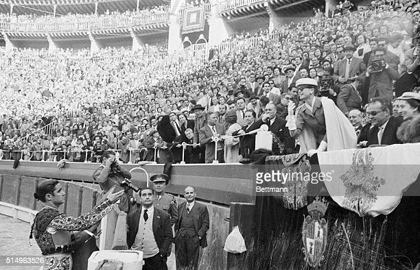 Princess Grace of Monaco tosses cap back to matador during a first class bullfight she and her bridegroom Prince Rainier III watched while stopping...