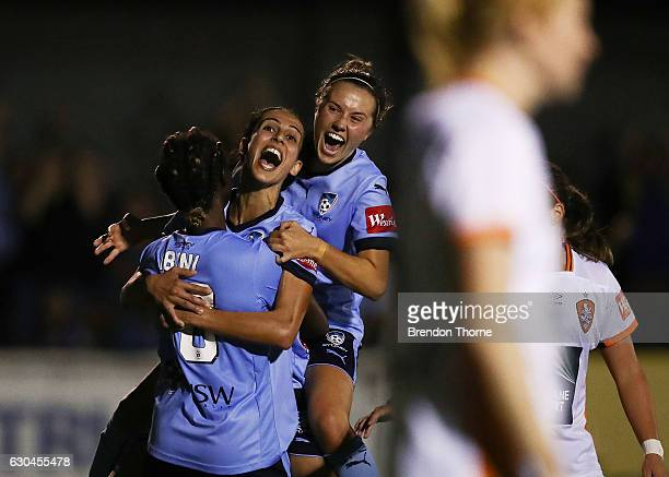 Princess IbiniIsei of Sydney celebrates with team mates Leena Khamis and Caitlin Foord after scoring a goal during the round eight WLeague match...