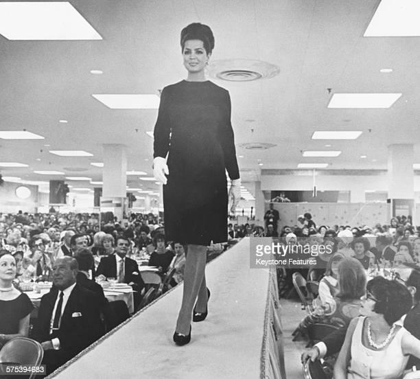 Princess Ira von Furstenberg walking down a runway modeling a black dress by Monsieur X at a fashion show circa 1965
