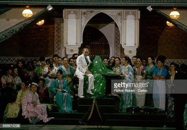 Princess Lalla Asmaa, draped in a green veil, is surrounded by a large wedding party shortly before her marriage to Khalid Bouchentouf. Her father,...